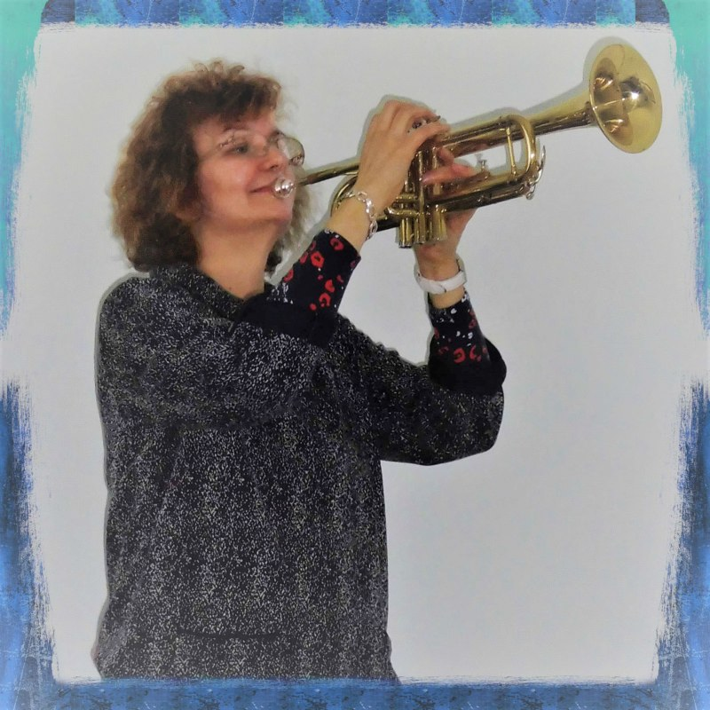 Penny Tedd music teacher, playing a trumpet instead of piano or cello.